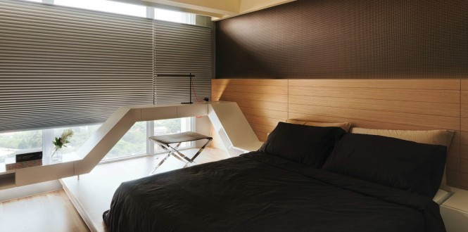 The platform bed of this room is framed in such a way that the headboard continues along the window wall acting as a desk and onto the opposite wall as a dresser.