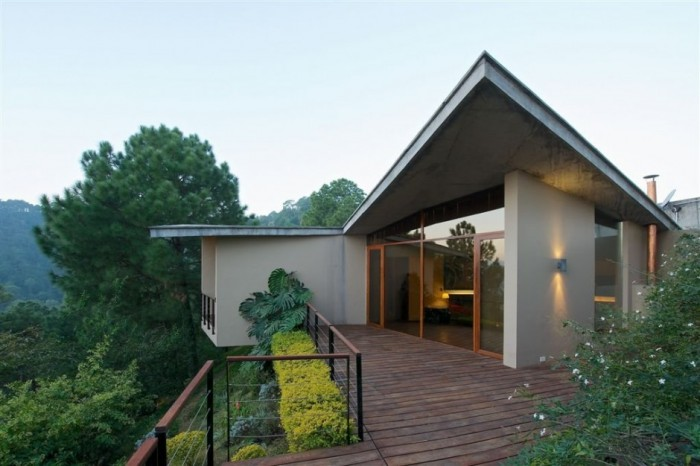 An origami-like roof, inspired by the surrounding mountain ranges, caps the structure of inclined concrete planes which encloses the three entrances, living room, dining room and kitchen.