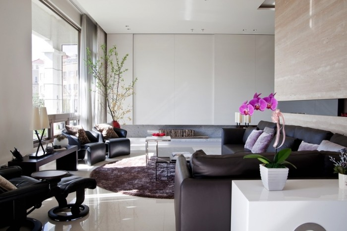 The marble walls and floor in this elegant contemporary living room are the perfect canvas for the violet furnishings and Asian inspired accents.