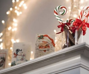 Christmas cards become charming mantel dcor along with a simple white lighted wreath.