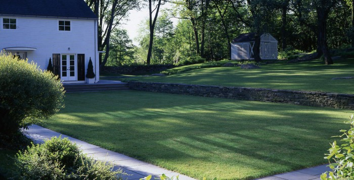 The stark contrast between this refined, manicured lawn and the uncontained wildness of the surrounding woods shows the diverse possibilities when landscaping in a country setting.
