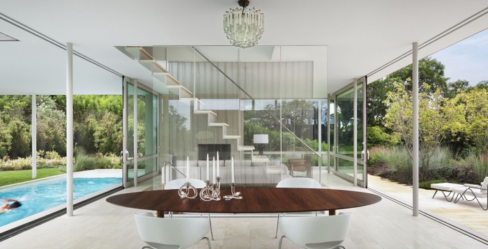 When open, the retractable glass walls of this modern minimalist home allow the homeowners to experience their indoor and outdoor worlds simultaneously.