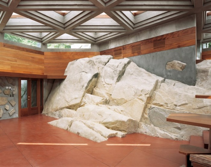 The foyer hosts a 60-ft wide by 12-ft high rock that dominates the complete left side of the space from its back wall to the front entry doors. The ceiling is a massive geometric wood structure with glass filling the spaces between.