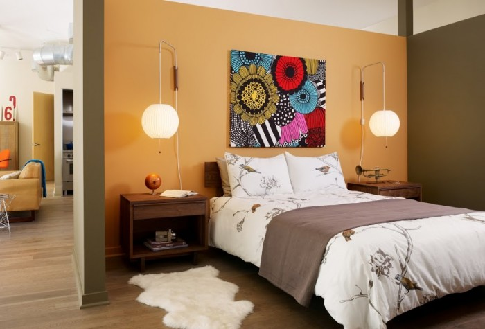 The bedroom in the couple's loft reflects an comfortable, open mindset with the bedroom freely opening into the living space. The sunflower walls offer a hint of femininity among other more manly elements.