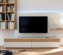 With its simple white finish and light unfinished wood accents, this simplistic media center is accompanied by a wall shelving unit.