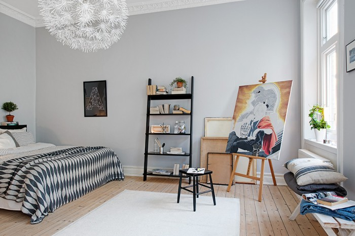 The bedroom is sparsely decorated allowing energy and lift to flow through the space creating a sense of tranquility and calm. Modern art set on an easel brings color to the otherwise white and black decor.