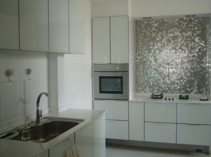Metallic mirrored tiles create a glamorous backsplash for a feminine kitchen decor.