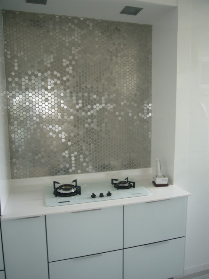 Metallic mirrored tiles create a glamorous backsplash for a feminine ...