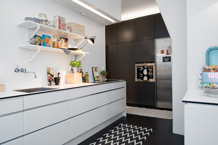 Featured in the kitchen are a wall of built-in appliances, sleek modern cabinetry, and plentiful work space.