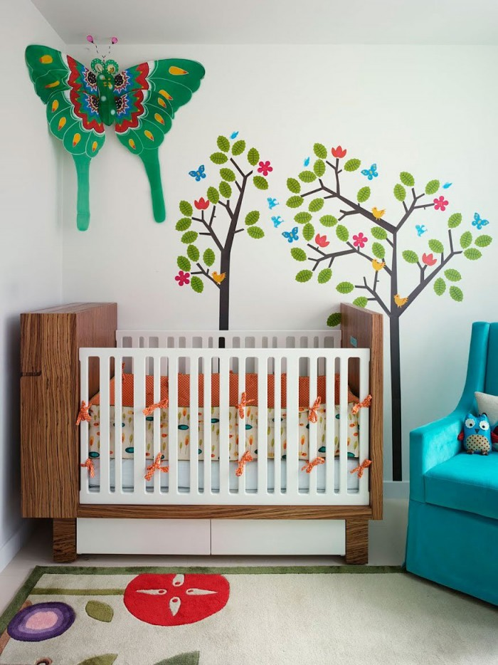 A colorful baby girl&#039;s nursery features a nature motif with trees on the walls, leaves on the bedding and a floral rug.