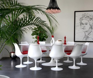 A large tulip style modern table and chair set creates a welcoming place to gather with family and friends over a nice meal.