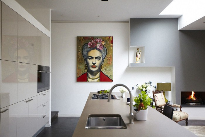 A modern painting of Frida Kahlo creates a focal point in the kitchen and living areas.