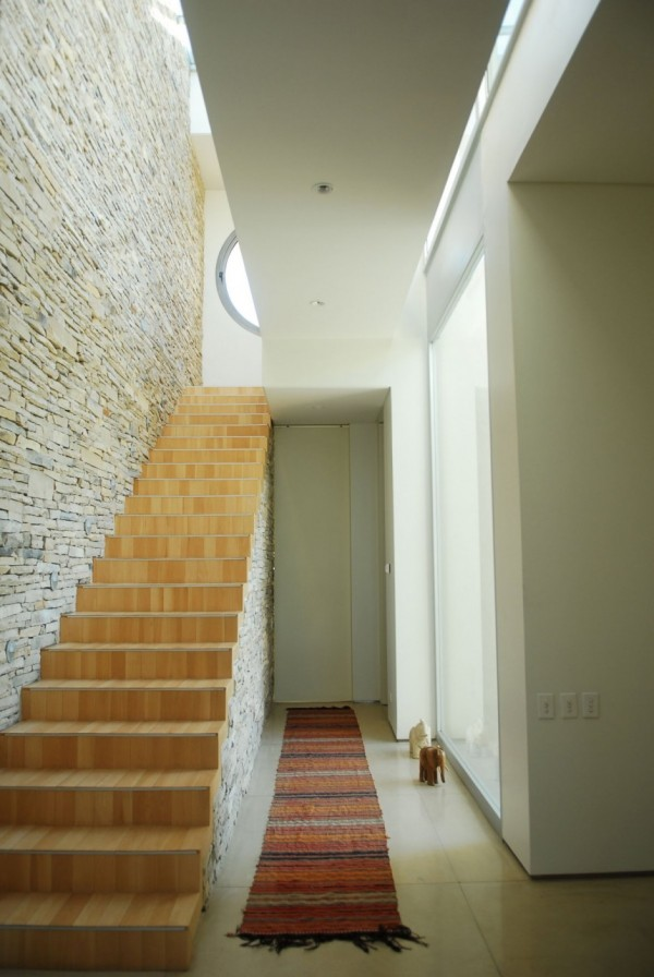 A wall of locally cut stone acts as a dramatic partition in the open plan living room and the primary material in the tactile twin bathroom. It continues into the organic, lightly wooded stairwell, which, without railings or glass panels, makes for a sleek design choice in a home where the safety of children, need not be considered. The stone is also a frequent reference for the warmly muted color palette used throughout Agua House's interior.     Dominated by stone as they are, internal spaces incorporate neutral colors and blonde wood in an effort to retain and reflect as much natural light as possible. External spaces, with the reflection of the pool and an aspect that enjoys ample sun, prefer a chic combination of dark wood and chrome that contrasts with the subtropical landscape and subsequently lush gardens.