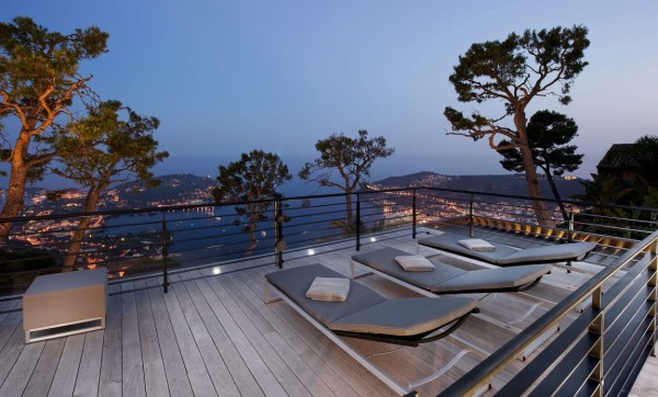 A lounge area is shown here at dusk with multiple loungers set upon a wood deck.