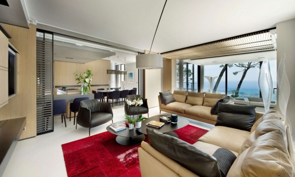 The living space is furnished with comfortable upholstered contemporary furnishings and pops of red accents.