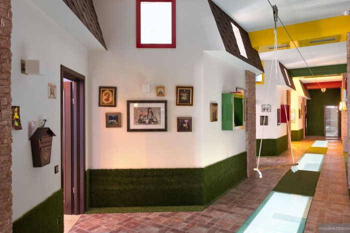 fun brightly colored hallway with swing and brick borders and paved flooring