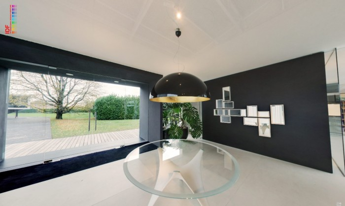 glossy black opaque pendant lit foyer with glass occasional table and mirrored feature wall
