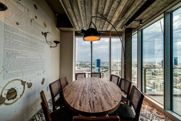 A rustic decorated conference room offers a quaint place to meet with views of the city below and beyond.