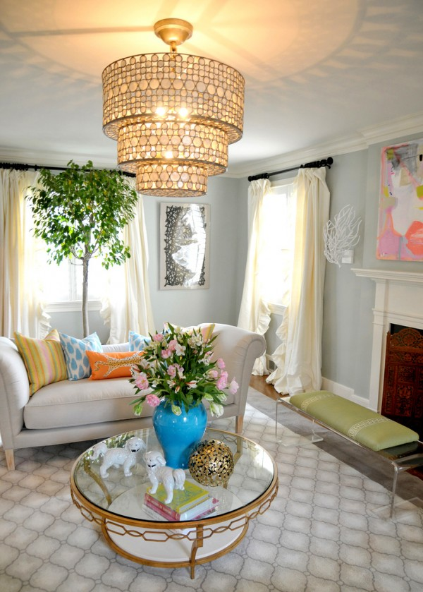 grand chandelier lit living with floral arrangement in blue urn