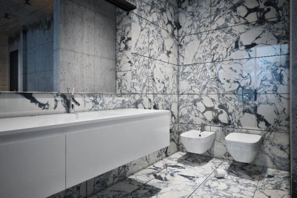 The master bathroom boasts walls and floors of dramatic marble in black, white and grey.