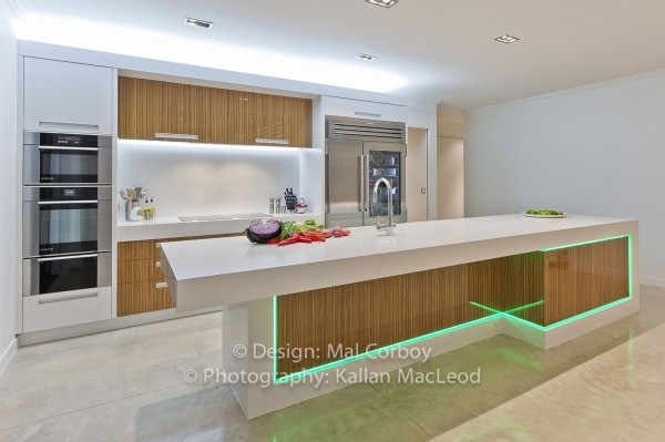Green LED lights add interest to a rather minimalist kitchen in wood and white.