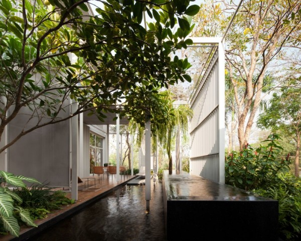 An outdoor living room created for dining uses a slatted wall and natural greenery for privacy.