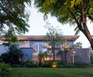 The modern house&#039;s exterior shows a boundless lawn filled with trees and greenery but no fences or walls.