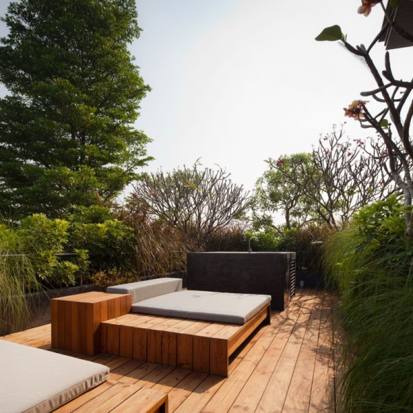 A small private lounge area is set atop a cedar platform and among tall green hedges for privacy.