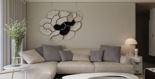 The living space is fitted with an inviting contemporary sofa with a dramatic modern art mosaic hanging above.