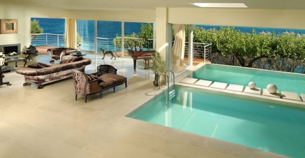 Two indoor and outdoor pools sit within the formal living room complete with piano and views of the sea beyond.