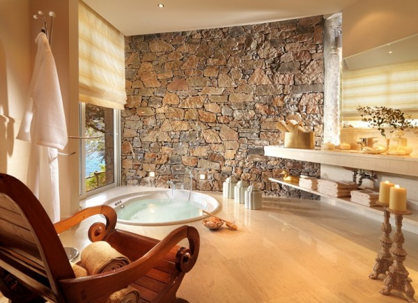The master bath suite boasts a stone wall and warm lighting for a wonderful bathing experience.