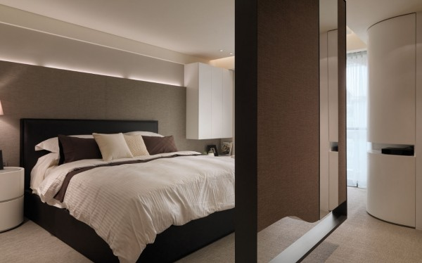 The master bedroom is designed with many notable architectural elements: the curved built-in closet, suspended dividing wall and fixed cabinetry.