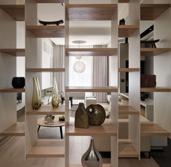 Built-in bookshelves of differing widths and shapes act as a dividing wall between staircase and living area.
