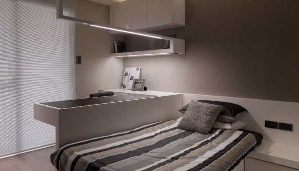 A guest room is fitted with a built-in desk unit with cabinets and adjoining twin bed. all decorated in white and grey tones.