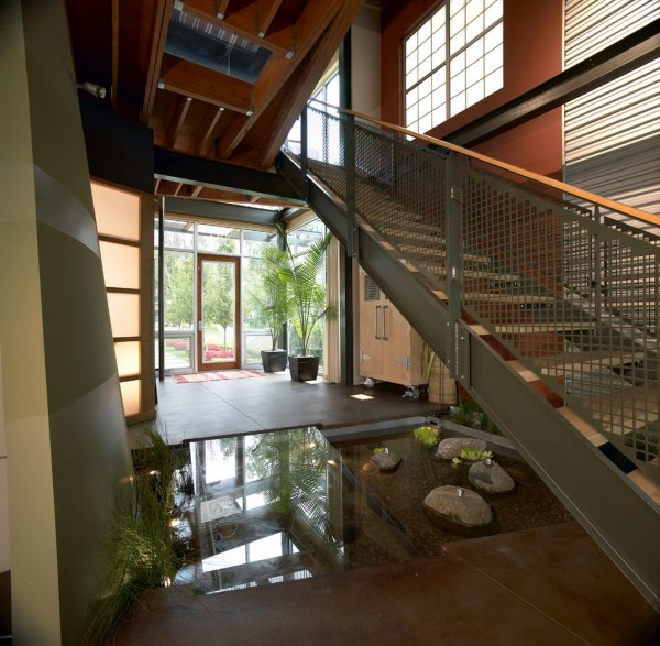 AZD takes the utilization of potentially dead space one step further by adding a glass floor atop the decorative body of water that lies beneath the stairs, creating a thoroughfare that serves as residence's main entry access. This space, like many to follow, is thoughtfully styled with living elements that take the form of water reeds and potted palms, which hints at an underlying ethos of tropical modernism that is seen in greater detail throughout this collection.