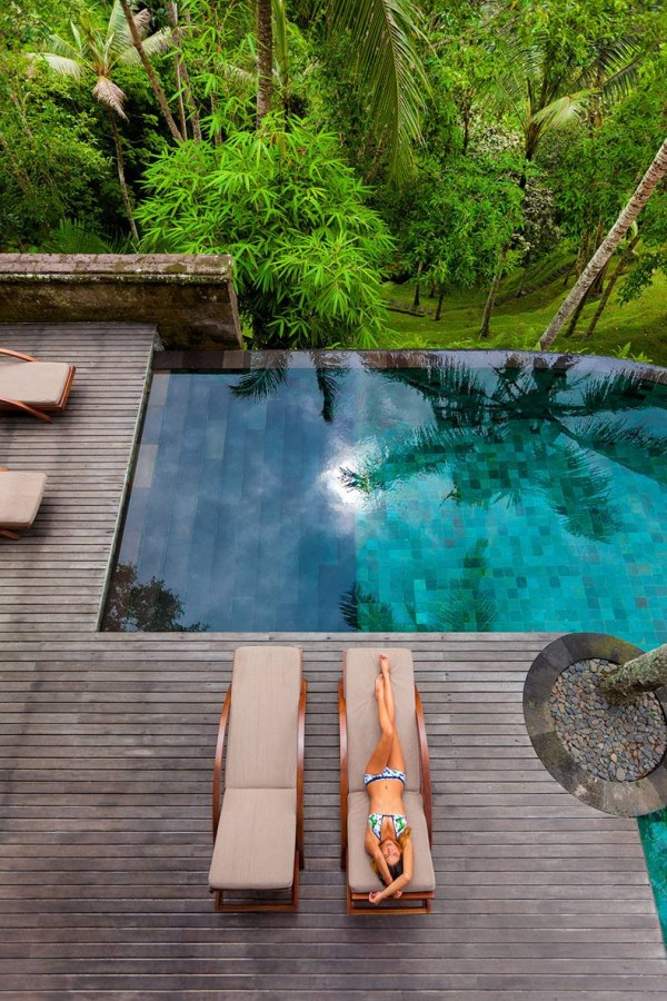 Como Shambhala Estate Bali- deckchairs and infinity pool with bamboo and palm forest views