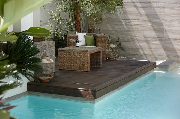 Custom Pool Area- close up of covered patio lounge surrounded by foliage