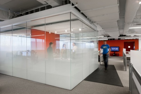 Though suitably compartmentalized, Kayak's headquarters, rather than feeling closed off, come across as a fundamentally open space, which one imagines, is how it should feel to feel to those who work within its, often glass, walls. The permeable nature of its more private interiors, such as meeting and conference rooms, use only a subtle frosted glazing to obscure the view of those outside and cocoon those working within only when seated. Though, in this way, the glass is highly functional, it is carried though the construction's entirety, serving a wholly more aesthetic purpose, in addition to rendering the space one in which employees can casually interact with each another.