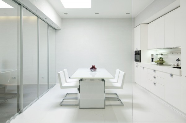One could be forgiven for branding the heart of this space 'open plan,' but the versatile glass walls act, not only, to define the space, but also set the tone for the ambiance generated by the entire project. They speak to the high shine finish of the white kitchen cabinetry, the metallic light installation that crowns the neutrally soft living area and hovers directly over its glass coffee table, are reflected in the glass that frames the recessed, wooded fireplace and paid tribute to in the miniature greenhouse niche that graces the bathroom.
