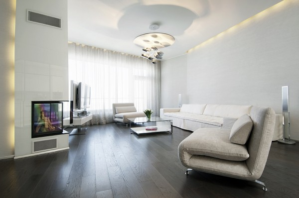 Living neutral soft furnishings with dark wood flooring modern lighting and glass fireplace niche