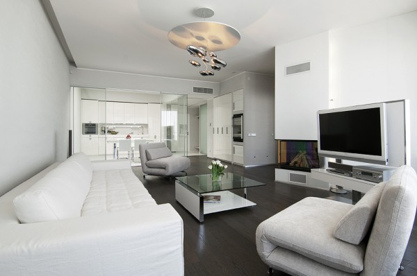 Living with neutral soft furnishings modern lighting dark wood flooring and view to glass kitchen