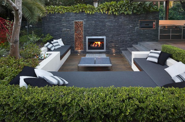 Outdoor Living with Sunken Lounge- lit fireplace in stone wall with hedging