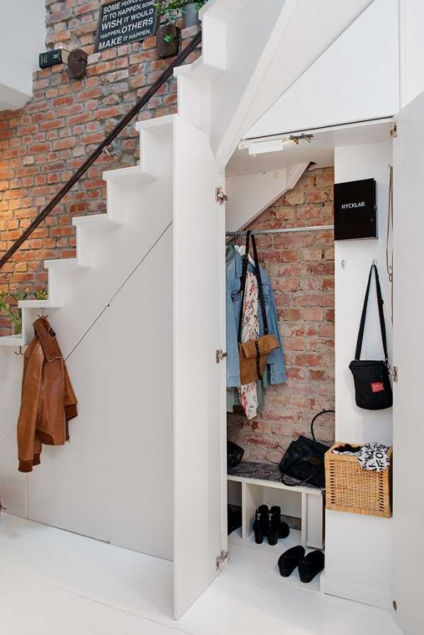 h Urban Apartment with Terrrace- storage under stairs against exposed brick wall