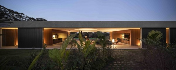 Marcio Kogan's Casa Lee Concrete House- exterior in the evening entrance with palms