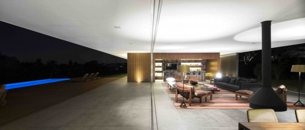 Marcio Kogan's Casa Lee Concrete House- glass walled indoor outdoor living with fireplace and wooden bar