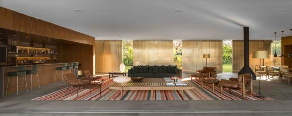 Marcio Kogan's Casa Lee Concrete House- open plan living with bar fireplace and curtained glass walls