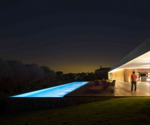 Marcio Kogan's Casa Lee Concrete House- pool at night with wooden decking
