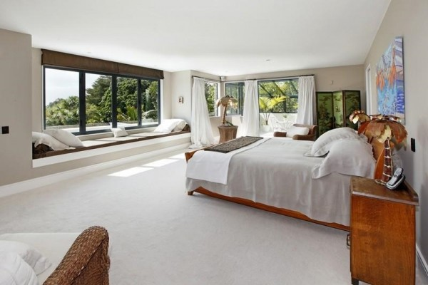 In both communal and private areas of the home, window seats are a popular inclusion. Minimally styled in white linen, this vantage point serves to frame New Zealand's famously varied vegetation, which is also celebrated inside the home by featuring several species of potted palms and ferns, such as that which inhabits the far corner of this, the master suite.