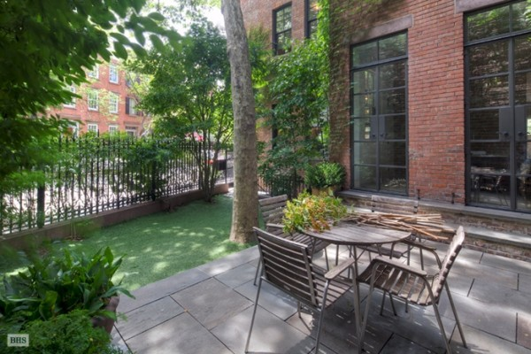 The backyard of Ms. Lebovitz's townhome is small yet intimate with a simple slat-wood table and chairs.