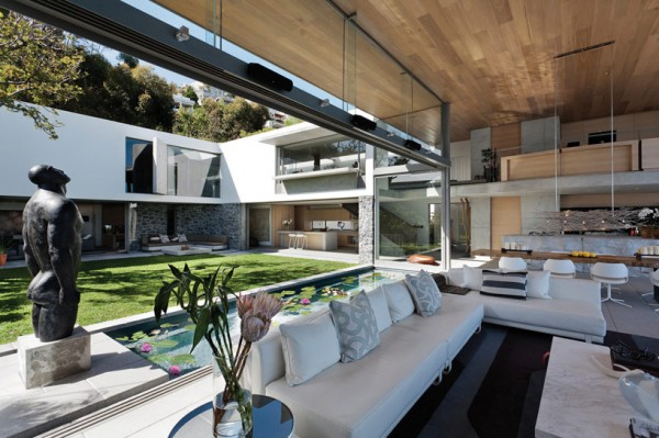 The open floor plan living/dining space is highlighted by a dynamic rich wood ceiling and an expanse of glass allowing unobstructed views of the courtyard beyond.